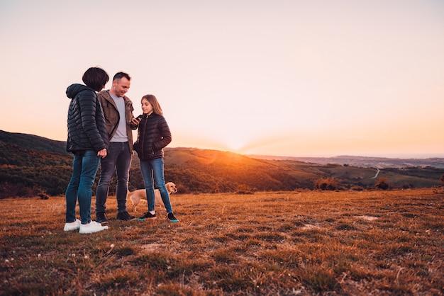 Família com cachorro em pé na colina e usando smartphone