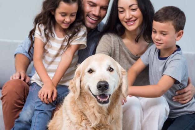 Família com cachorro na sala de estar