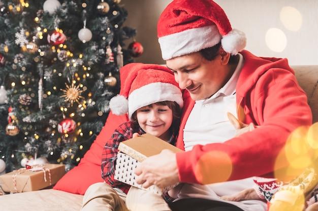 Família com chapéu de papai noel, pai e filho abrem presente de natal em casa