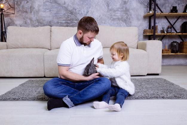 Família com coelho em casa no tapete perto do sofá.