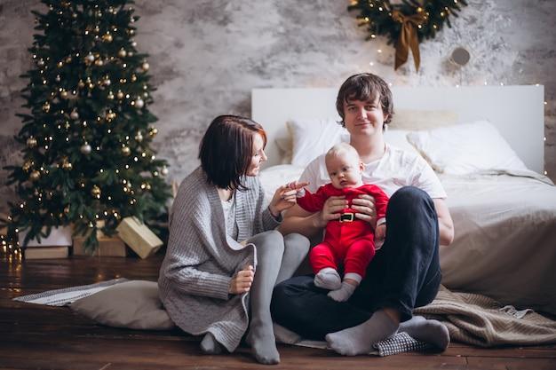 Família com criança bebê sentado perto de árvore de natal em casa