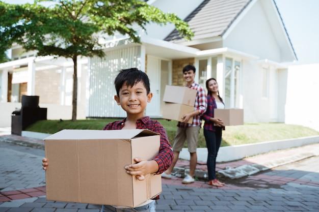 Família com criança em pé na frente de sua casa