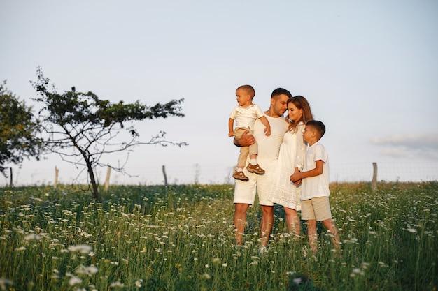Família com criança pequena bonita. pai em uma camiseta branca. fundo do sol.