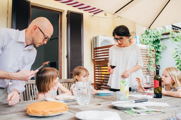 Família com crianças ao ar livre sentado mesa tomando café da manhã