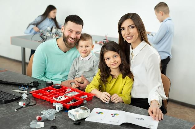 Família com crianças em um clube de robótica faz um robô controlado por um construtor.