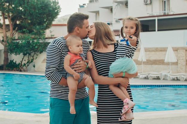 Família com crianças posando na piscina. férias no hotel