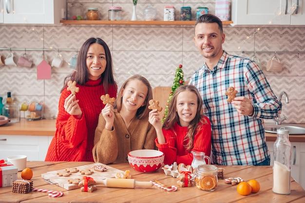 Família com crianças preparando biscoitos para o natal na cozinha. feliz natal e boas festas.
