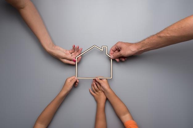 Família com crianças segurando a estrutura de uma casa em um fundo cinza