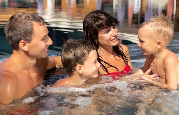 Família com dois filhos aproveitando o dia na piscina