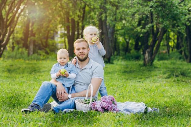 Família com dois filhos descansar no jardim de verão