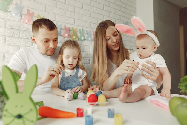 Família com dois filhos em uma cozinha se preparando para a páscoa