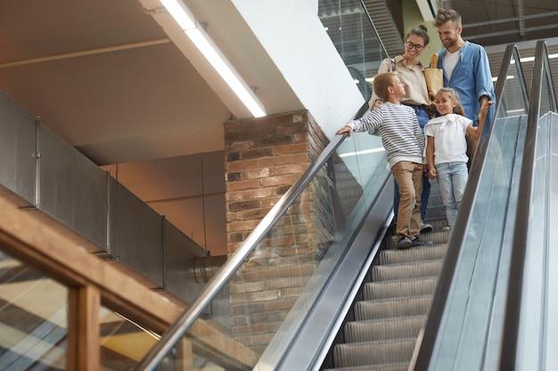 Família com dois filhos indo escada rolante