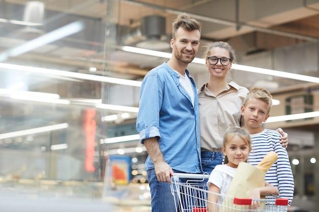 Família com dois filhos posando no supermercado