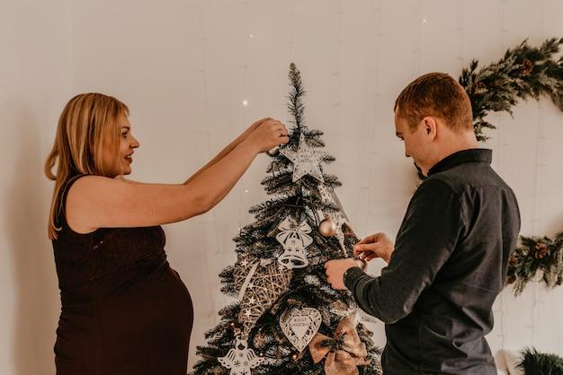 Família com esposa grávida decora a casa para o ano novo. manha de natal. interior. celebração do dia dos namorados