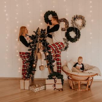 Família com esposa grávida na escada decora a casa para a menina de ano novo bebê sentado em uma cadeira e brincando. manha de natal. interior de ano novo. comemoração do dia dos namorados