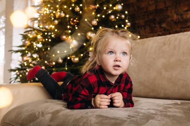 Família com filha celebram o natal em casa perto da árvore e trocam presentes