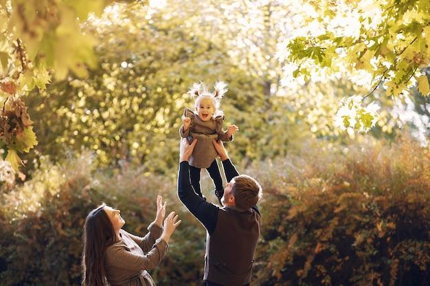 Família com filha em um parque de outono