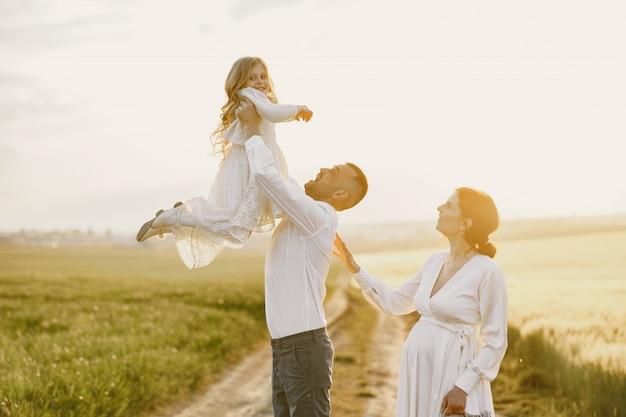 Família com filha passando um tempo juntos no campo ensolarado