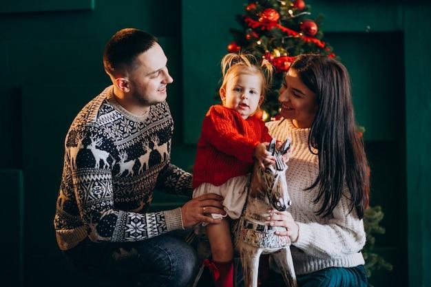 Família com filha pela árvore de natal brincando com pônei de madeira