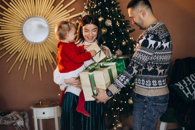 Família com filha pela árvore de natal desembalar caixa de presente