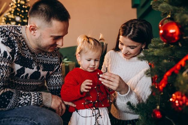 Família com filha pendurar brinquedos na árvore de natal