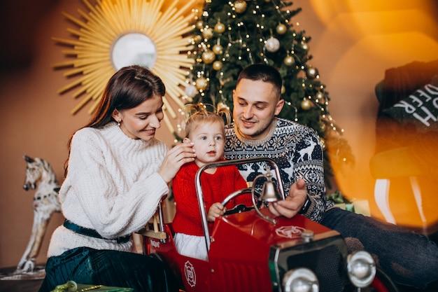Família com filha pequena com presente de natal pela árvore de natal