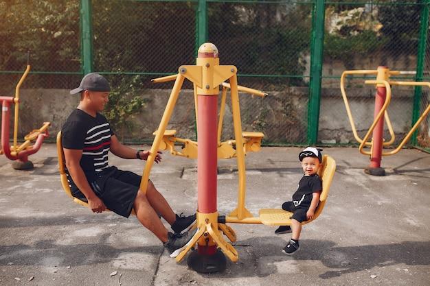 Família com filho pequeno a brincar num parque infantil