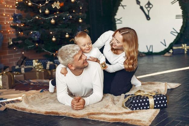 Família com filho pequeno em casa perto da árvore de natal