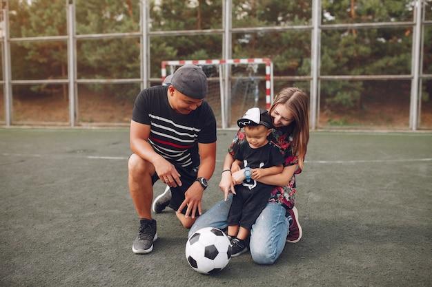 Família com filho pequeno jogando futebol