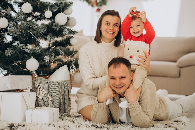 Família com filho pequeno no natal perto da árvore de natal em casa