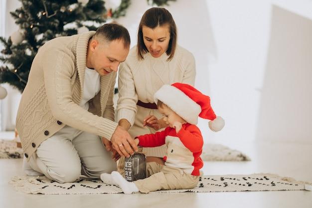 Família com filho pequeno perto da árvore de natal em casa