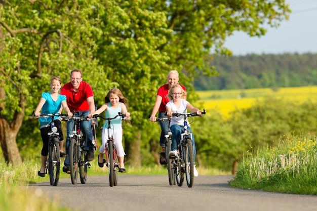 Família com filhos, andar de bicicleta no verão com bicicletas