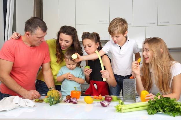 Família com filhos corta vegetais para cozinhar