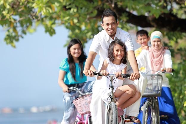 Família com filhos gosta de andar de bicicleta ao ar livre na praia