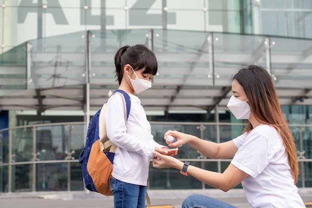 Família com filhos na máscara facial em um shopping. mãe e filha usam máscara durante o surto de coronavírus e gripe. proteção contra vírus e doenças, desinfetante para as mãos em um local público lotado.
