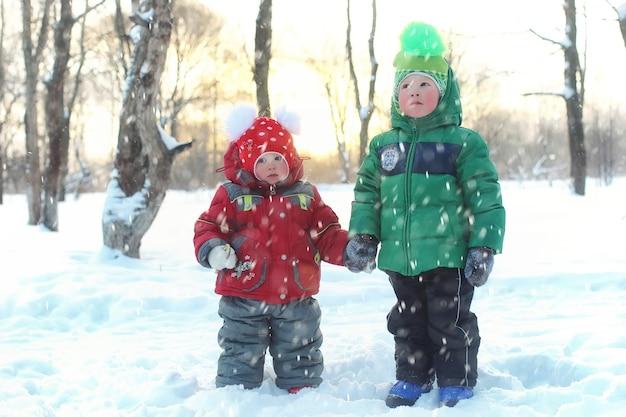 Família com filhos no parque durante nevasca de inverno