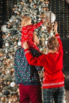 Família com filhos nos braços alegram-se perto da árvore de natal no natal