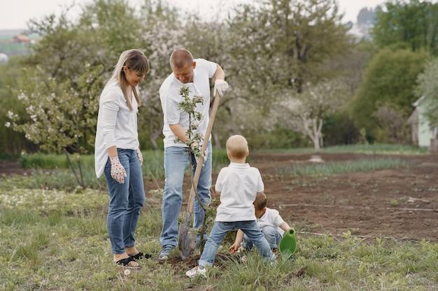 Família com filhos pequenos estão plantando uma árvore em um quintal