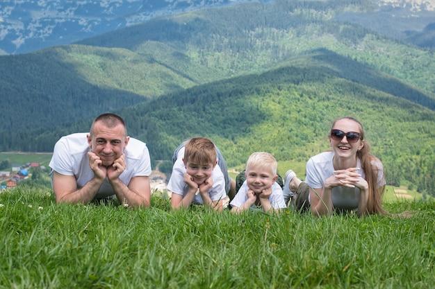 Família com filhos situa-se na grama. montanhas ao fundo.