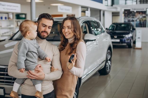 Família com garota bbay escolhendo um carro em um salão de carros Foto gratuita