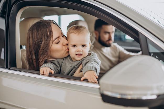 Família com garota bbay escolhendo um carro em um salão de carros