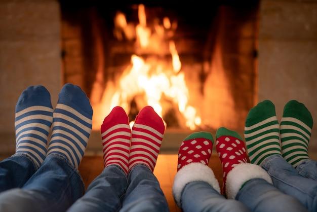 Família com meias de natal perto da lareira mãe, pai e filhos se divertindo juntos