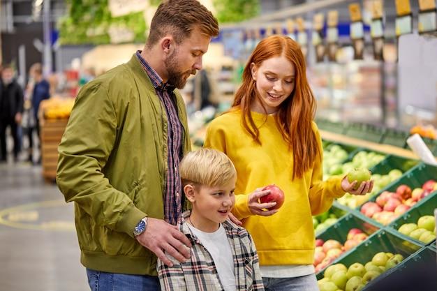 Família com menino criança na loja de alimentos, pais caucasianos e criança comprando maçãs de frutas frescas, discutindo