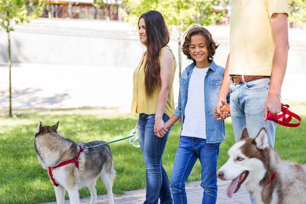 Família com menino e cachorro no parque juntos