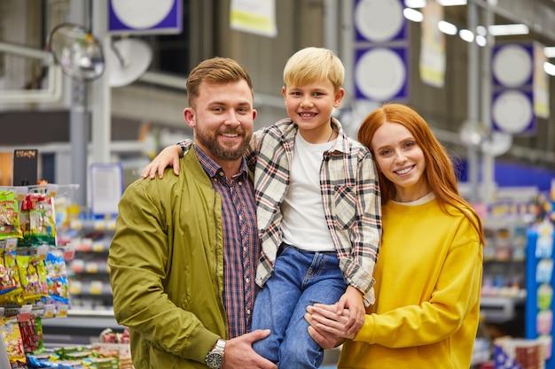 Família com o filho no supermercado, os jovens pais seguram o menino bonito nas mãos e sorriem, prateleiras com produtos