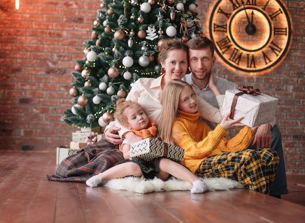 Família com presentes de natal em uma aconchegante sala de estar.