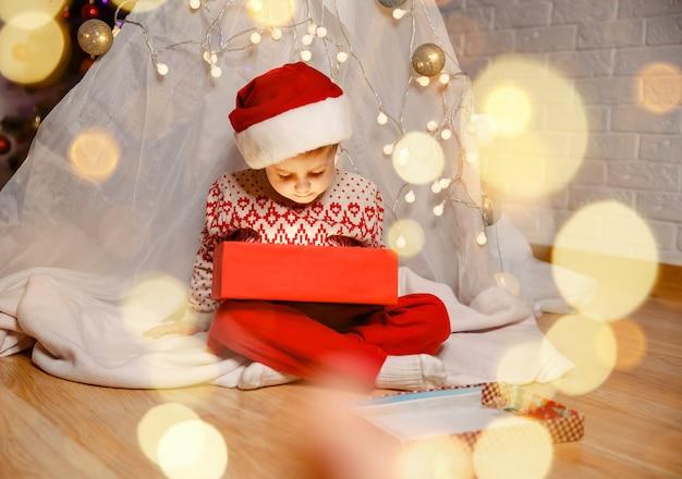 Família com presentes na véspera de natal, menino engraçado deitado no chão com um presente