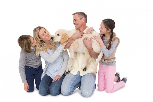 Família com seu cão posando e sorrindo para a câmera juntos
