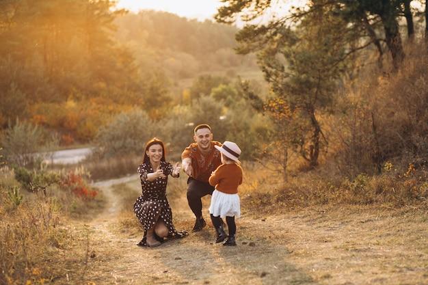 Família com sua filha pequena em um campo de outono