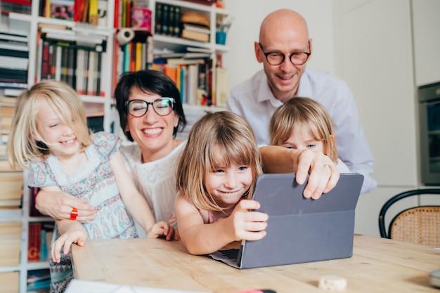 Família, com, três crianças, indoor, usando, tabuleta